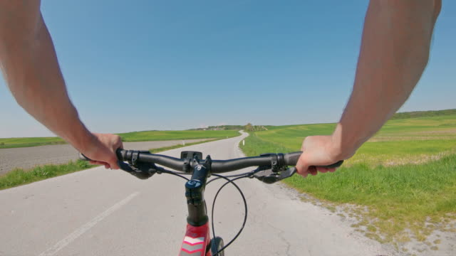 ms personal perspektive mann radfahren auf sonnigen landstraße - moving past stock-videos und b-roll-filmmaterial