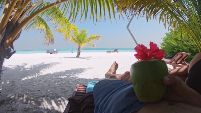 ms personal perspective man relaxing with coconut drink on idyllic tropical beach,maldives - lying down stock videos & royalty-free footage