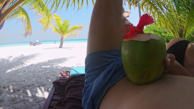 cu personal perspective man relaxing with coconut drink on idyllic,tropical beach,maldives - tropical drink stock videos and b-roll footage