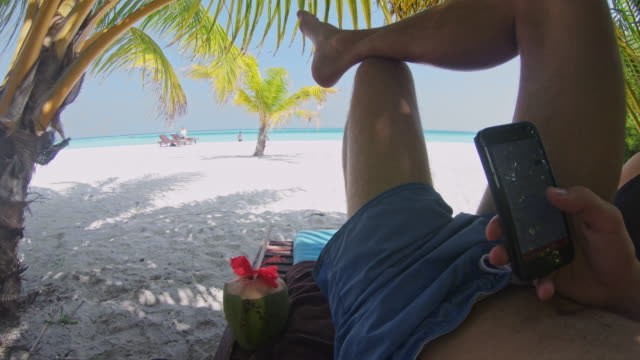 ms personal perspective man relaxing,using smart phone on tranquil tropical beach,maldives - remote location phone stock videos & royalty-free footage