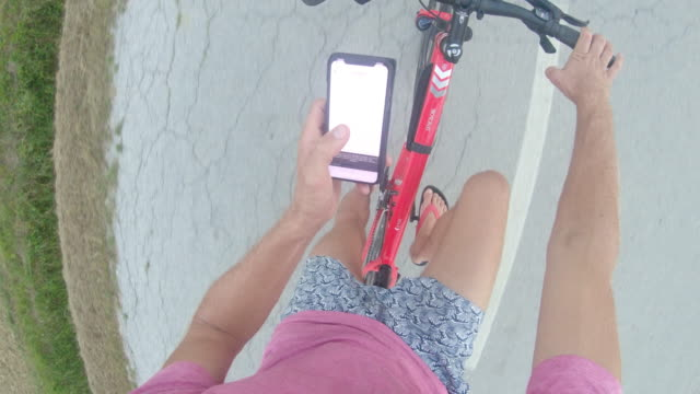 ms personal perspective man using smart phone while riding bicycle - multitasking stock videos & royalty-free footage