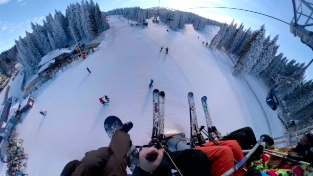 personal perspective od a snowboarder riding on a ski lift - seggiovia video stock e b–roll