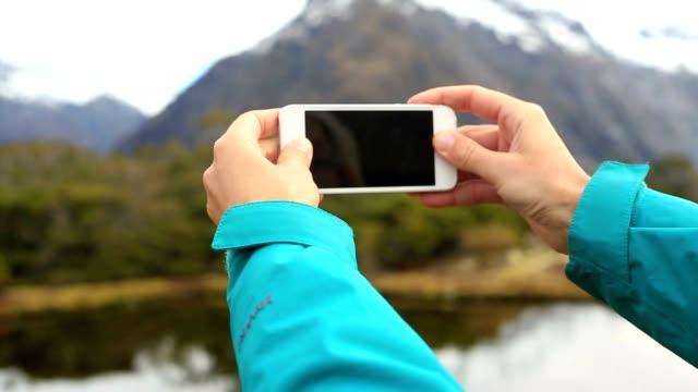Persönlichen Perspektive einer Frau Wandern und fotografieren Smartphone See Berglandschaft