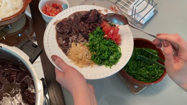 vídeos de stock, filmes e b-roll de perspectiva pessoal de uma mulher servindo um prato de prato tradicional brasileiro - feijoada em casa - almoço
