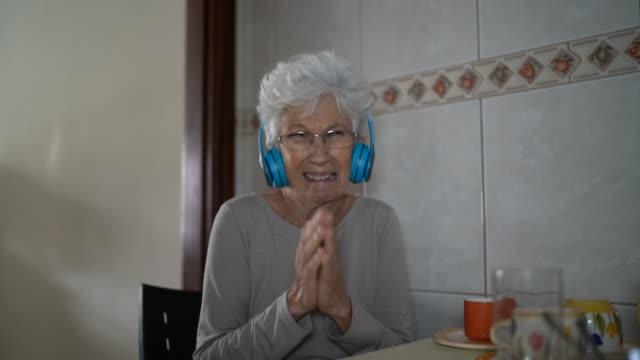 stockvideo's en b-roll-footage met persoonlijk perspectief van een hogere vrouw die aan haar sociale mediavolgers thuis spreekt - jong van hart