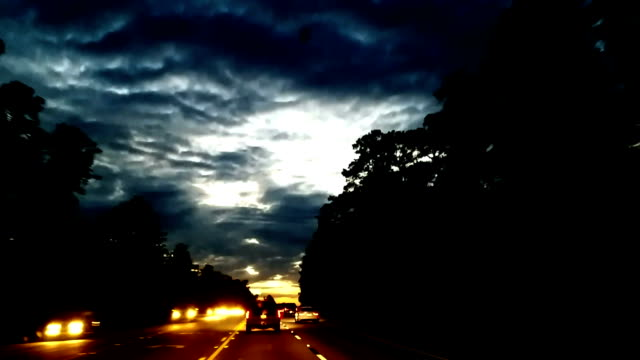Personal perspective of driving on street at dusk.