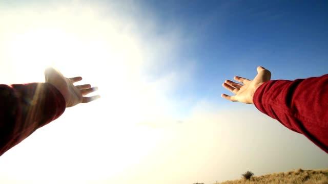 Persönliche Perspektive der Person auf Berggipfel über Wolken