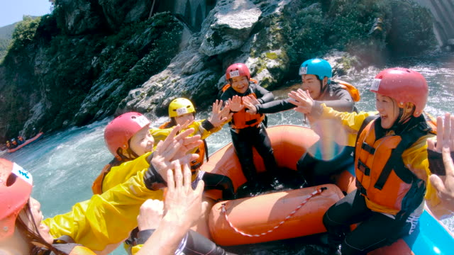 personal point of view of a group of people celebrating success while white water river rafting - terreno accidentato video stock e b–roll