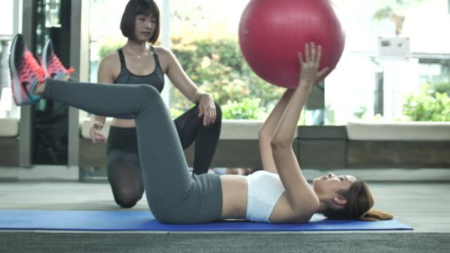 vídeos y material grabado en eventos de stock de entrenador personal y atractiva mujer haciendo ejercicio con bola de la aptitud - pilates