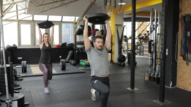 personal trainer and ladies on weightlifting training in gym - lunge stock videos & royalty-free footage