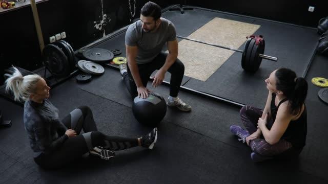 personal trainer e due donne che si rilassano dopo l'allenamento - cura della persona video stock e b–roll