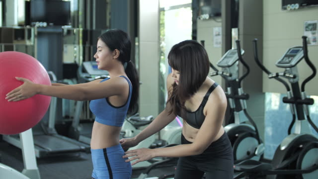 personal trainer and woman using fitness ball for stretching exercise in fitness class - fitness ball stock videos & royalty-free footage