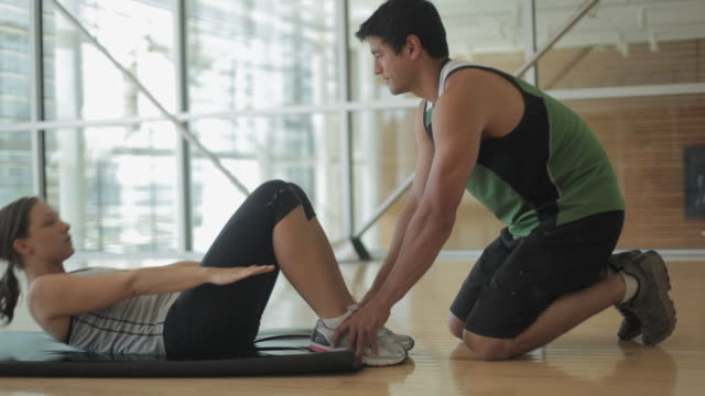 ms ds personal trainer assisting woman on mat floor for sit-ups in gym - sit ups stock videos & royalty-free footage