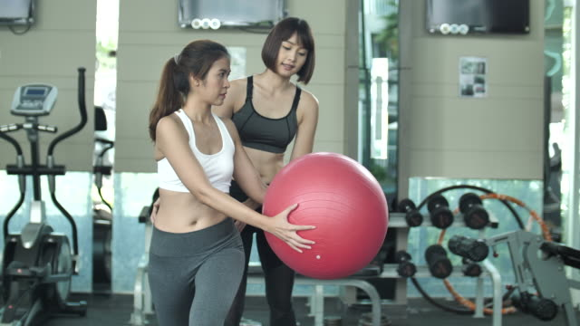 personal trainer guiding woman doing exercising on fitness ball in gym - pallone per fitness video stock e b–roll