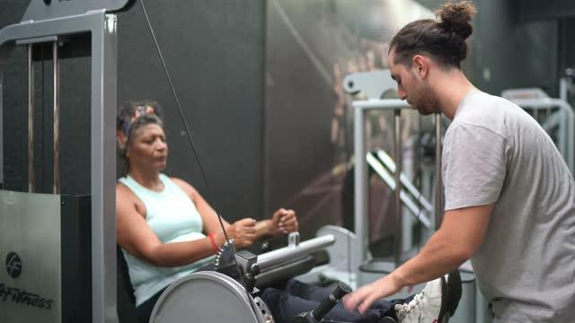 vídeos de stock, filmes e b-roll de personal trainer ajudando idosa se exercitando na academia - treino esportivo