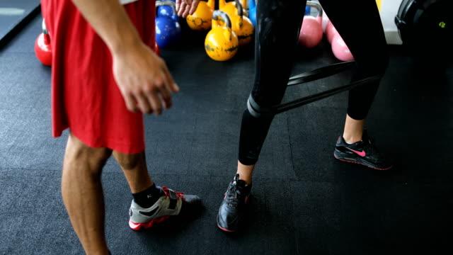 vídeos de stock, filmes e b-roll de personal trainer na academia de ginástica - instrutor de fitness