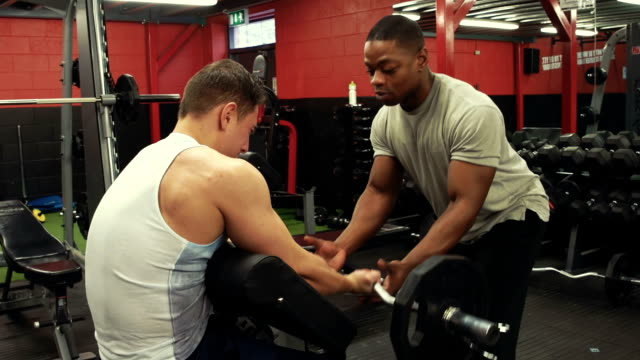 personal trainer in the gym weight training - strength training stock videos & royalty-free footage