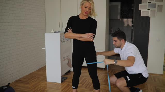 Personal trainer measuring woman in gym