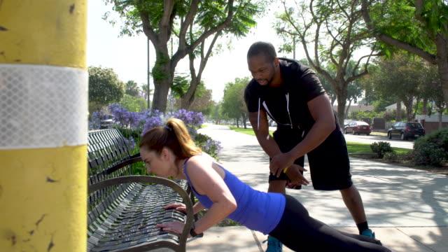 vídeos de stock, filmes e b-roll de treinador pessoal motiva o cliente a fazer flexões - instrutor de fitness