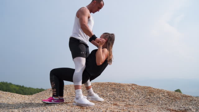 Personal trainer motivates client while exercise