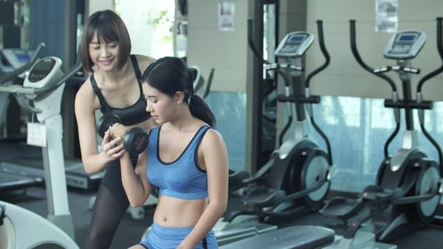 vidéos et rushes de personal trainer ou kinésithérapeute travaille avec le client dans la salle de gym - poids pour la musculation