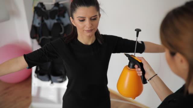 personal trainer preparing woman for ems training - body abbigliamento sportivo video stock e b–roll