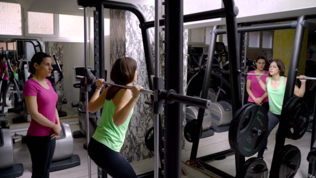 personal trainer shows exercise to his client - durevolezza video stock e b–roll
