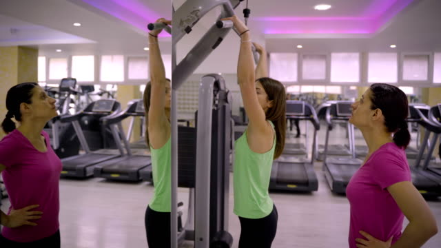 a personal trainer shows his client a shoulder training in the gym - durevolezza video stock e b–roll