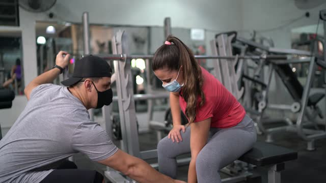 personal trainer supporting a young woman in the gym using face mask - hand weight stock videos & royalty-free footage