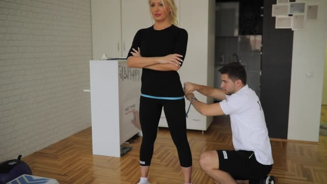 personal trainer taking woman's measurements before training - tape measure stock videos & royalty-free footage