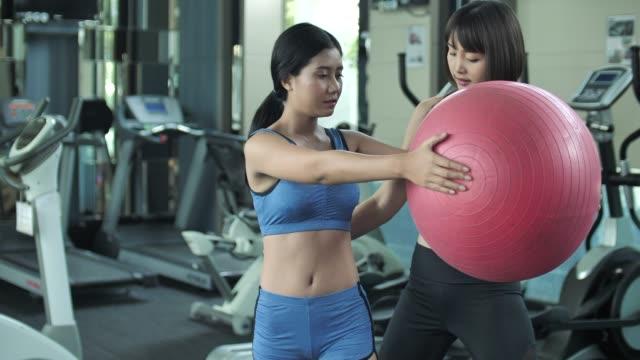 vídeos de stock, filmes e b-roll de cliente de ensino instrutor pessoal como exercício com bola de yoga - instrutor de fitness