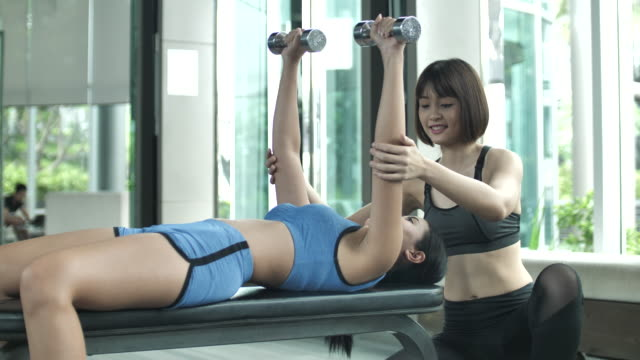 Personal trainer weight training with her customer