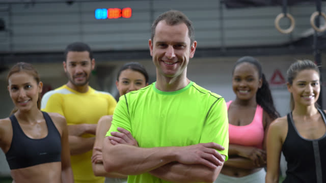 Personal trainer with arms crossed and group of people behind