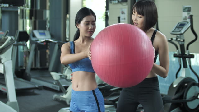 Personal training training with fitness ball in gym