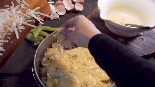 personal view of a woman preparing an oven dish: adding cheese - cheese stock videos & royalty-free footage
