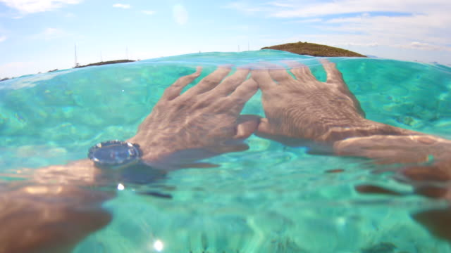 personal view of guy swimming inside crystal water in the paradise island of formentera in spain. - transparent stock videos & royalty-free footage