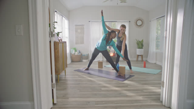 SLO MO. Personal yoga instructor helps African American woman transition from extended side angle to triangle pose using block for support.