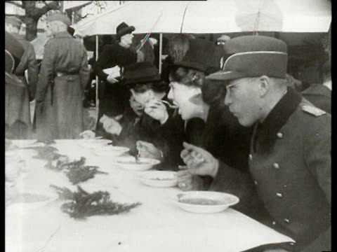 personnel of the fieldkitchen of the german wehrmacht prepare soup for adults and children seyssinquart arrives and joins the group - wehrmacht stock-videos und b-roll-filmmaterial