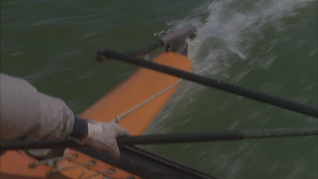 A person's arm controlling the tiller on a sailboat moving through water.