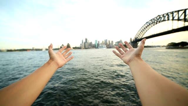 Person's arms stretch towards Sydney skyline, Australia