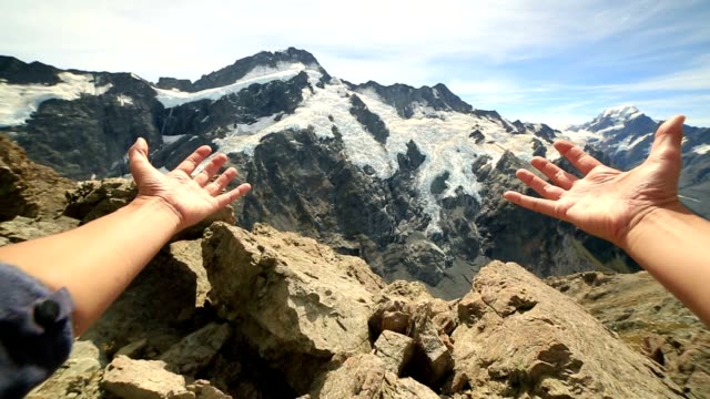 Person's arms stretches towards the Mount Cook