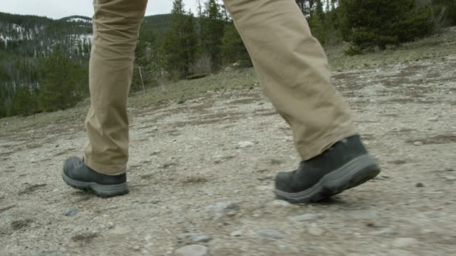 a person's feet in hiking boots hike in the rocky mountains of colorado under an overcast sky in winter - stivale video stock e b–roll