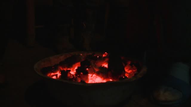 cu person's feet warming at pot of burning coal, datong, sichuan, china - burning coal stock videos & royalty-free footage