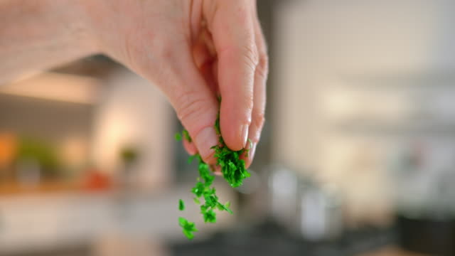 slo mo td person's fingers sprinkling chopped parsley - tilt down stock videos & royalty-free footage