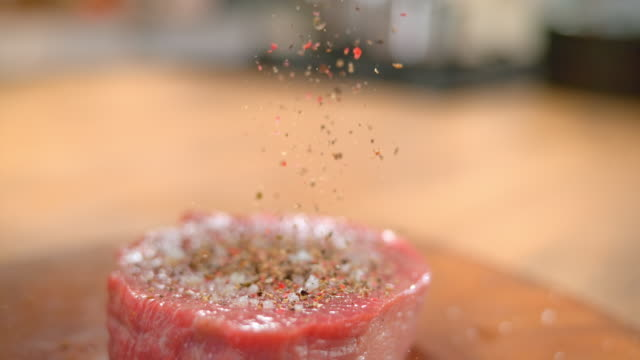 slo mo td person's fingers sprinkling ground pepper onto a piece of red meat - tilt down stock videos & royalty-free footage