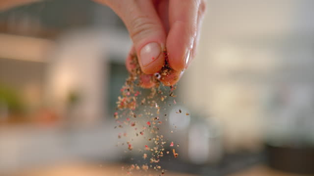 slo mo ld person's fingers sprinkling ground pepper - season stock videos & royalty-free footage