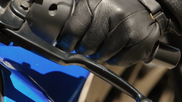 cu person's hand in leather glove squeezing motorcycle brake, los angeles, california, usa - glove stock videos and b-roll footage