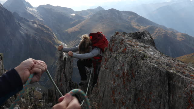 vídeos de stock e filmes b-roll de person's hands belaying young woman to mountain summit - corda de trepar