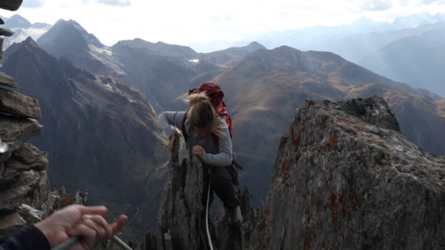 person's hands belaying young woman to mountain summit - belaying stock videos & royalty-free footage