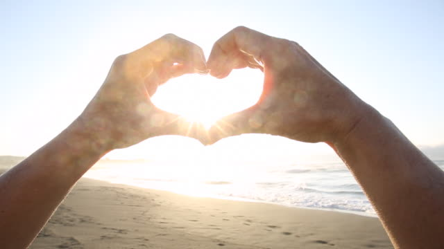 Person's hands form heart shape above ocean surf, sunset